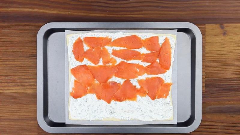 Розподіліть сирний крем по тісту, викладіть скибочки сьомги.