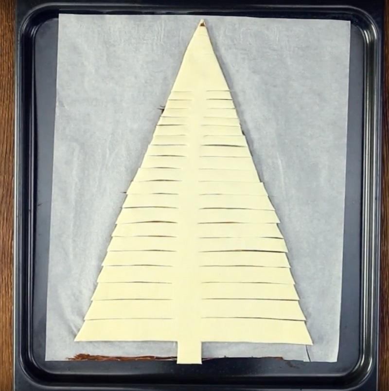 Виріжте внизу стовбур дерева шириною 3 см. Потім робіть надрізи через кожні 2 см по краях тісту, як на фото.